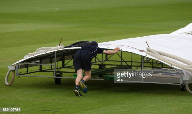 A member of the ground staff pushes the covers as rain stops play at the ICC Champions Trophy Warmup match between India and New Zealand at The Oval...