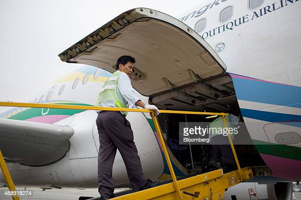A member of the ground staff stands on a ramp positioned next to a Bangkok Airways Co Airbus SAS A319 aircraft at Hong Kong International Airport in...