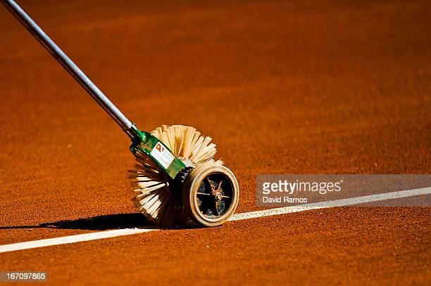 A member of the ground staff sweeps clay dust from the court lines before the first match of the Fed Cup World Group Play off at the Real Club de...