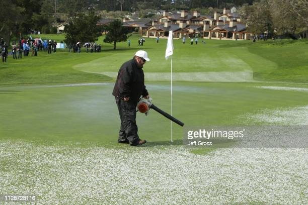 A member of the grounds crew clears hail from the first green during the final round of the ATT Pebble Beach ProAm at Pebble Beach Golf Links on...
