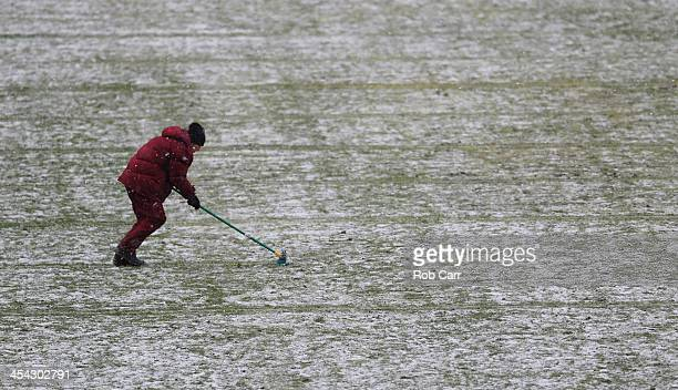 A member of the grounds crew clears snow off the field during the second quarter of the Washington Redskins and Kansas City Chiefs game at FedExField...