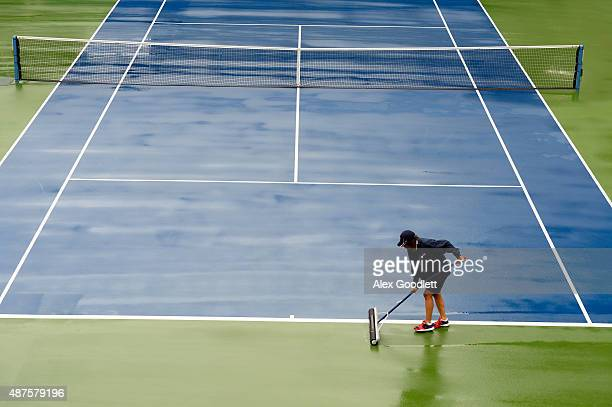 A member of the grounds crew squeegees the court dry after rain on Day Eleven of the 2015 US Open at the USTA Billie Jean King National Tennis Center...