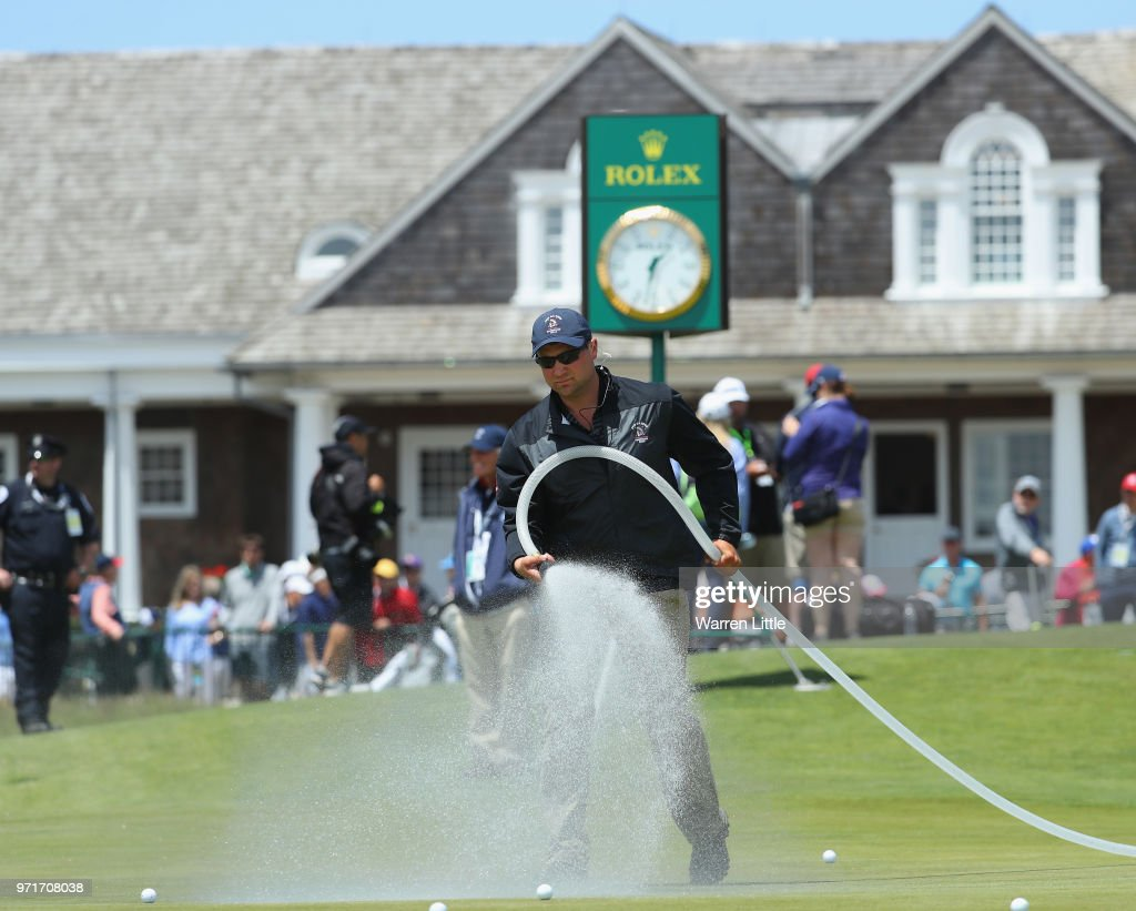 A member of the grounds crew waters a green during practice rounds prior to the 2018 U.S. Open at Shinnecock Hills Golf Club on June 11, 2018 in Southampton, New York.