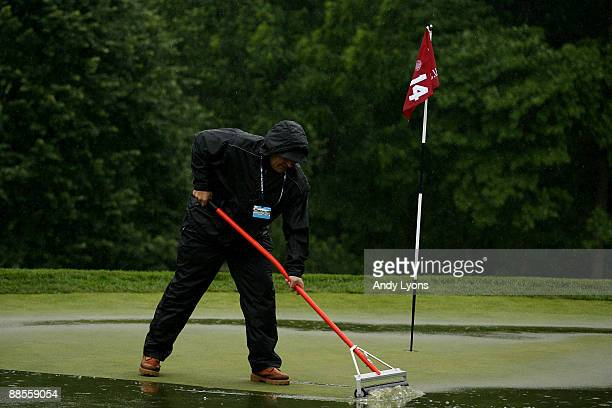 Member of the grounds staff works on the 14th green during the first round of the 109th U.S. Open on the Black Course at Bethpage State Park on June...