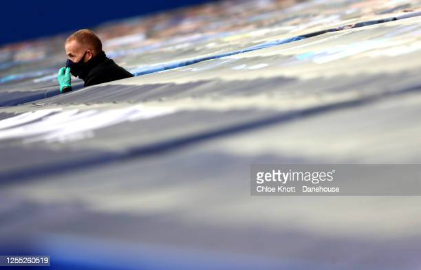 A member of the grounds team sits in the stands during the Premier League match between Everton FC and Southampton FC at Goodison Park on July 09...