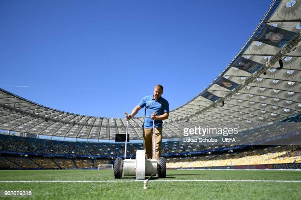 A member of the groundsmen staff paints the lines prior to the UEFA Champions League Final between Real Madrid and Liverpool at NSC Olimpiyskiy...