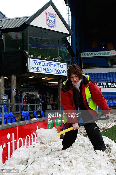 A member of the groundstaff clears snow inside the stadium ahead of the npower Championship match between Ipswich Town and Swansea City at Portman...