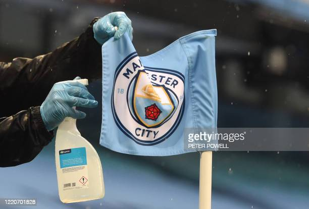 TOPSHOT A member of the groundstaff sprays a corner flag with a disinfectant during the English Premier League football match between Manchester City...