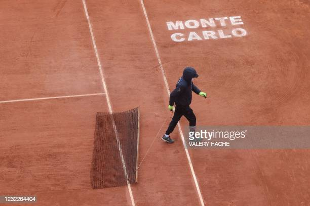 Member of the groundstaff sweeps the court following a break due to rain during the Italy's Lorenzo Musetti vs Russia's Aslan Karatsev first round...