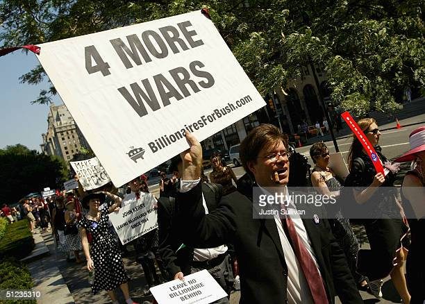 A member of the group 'Billionaires for Bush' holds a sign as he marches down 5th Avenue during a protest march August 29 2004 in New York City...