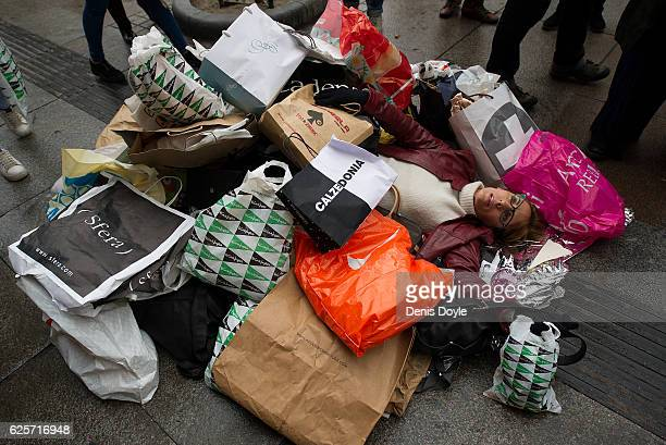 A member of the group 'Ecologists in Action' lies amongst a pile of shopping bags during a street performance to protest against the allegedly...