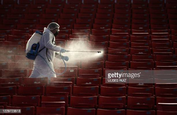 Member of the Guadalajara staff disinfects the stands before the start of the repechage football match of the Mexican Apertura tournament between...