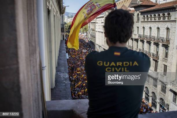 A member of the Guardia Civil waves a Spanish national flag during a protest for Spanish unity on the Via Laientana in Barcelona Spain on Sunday Oct...