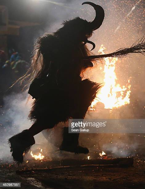 A member of the Haiminger Krampusgruppe dressed as the Krampus creature hits a fire to release sparks on the town square during their annual Krampus...