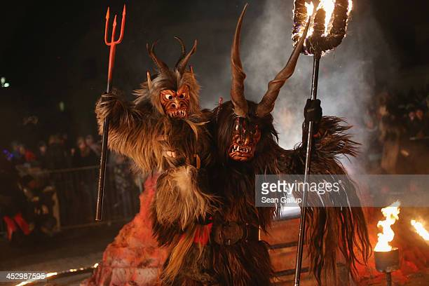 Member of the Haiminger Krampusgruppe dressed as the Krampus creature holds a junior Krampus that in the performance had been transformed from a...
