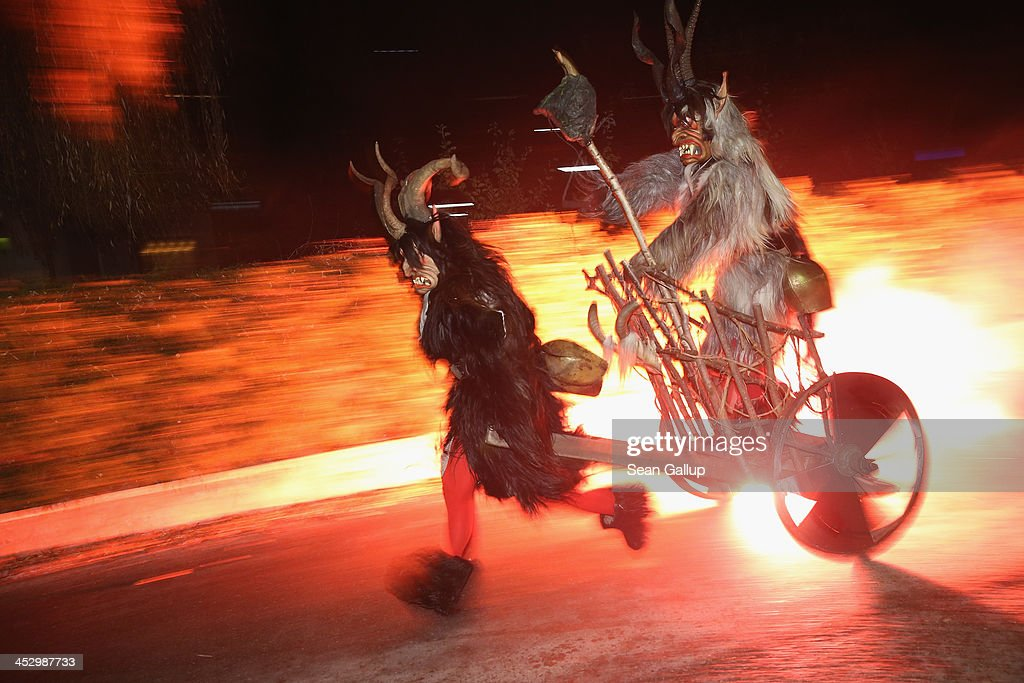 A member of the Haiminger Krampusgruppe dressed as the Krampus creature pulls another on a fiery cart to the town square during the annual Krampus night in Tyrol on December 1, 2013 in Haiming, Austria. Krampus, in Tyrol also called Tuifl, is a demon-like creature represented by a fearsome, hand-carved wooden mask with animal horns, a suit made from sheep or goat skin and large cow bells attached to the waist that the wearer rings by running or shaking his hips up and down. Krampus has been a part of Central European, alpine folklore going back at least a millennium, and since the 17th-century Krampus traditionally accompanies St. Nicholas and angels on the evening of December 5 to visit households to reward children that have been good while reprimanding those who have not. However, in the last few decades Tyrol in particular has seen the founding of numerous village Krampus associations with up to 100 members each and who parade without St. Nicholas at Krampus events throughout November and early December.