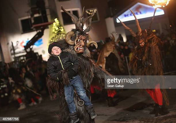 A member of the Haiminger Krampusgruppe dressed as the Krampus creature holds a delinquent little boy whom the Krampus will take to Hell to transform...