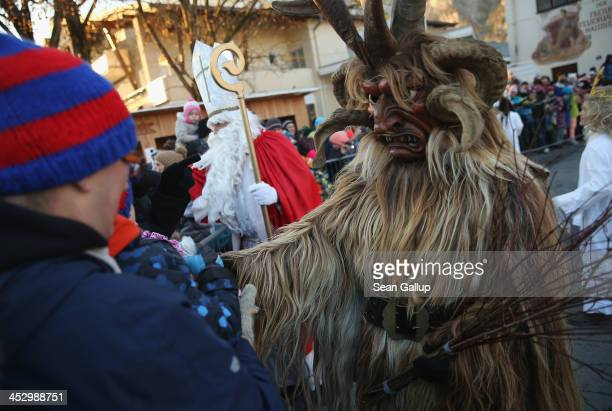 Member of the Haiminger Krampusgruppe dressed as the Krampus creature accompanies St. Nicholas and angels distributing sweets to children prior to...