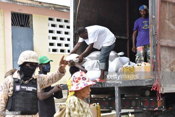 Member of the Haitian National Police directs residents waiting in line to receive bags of rice and cooking oil at a World Food Programme...