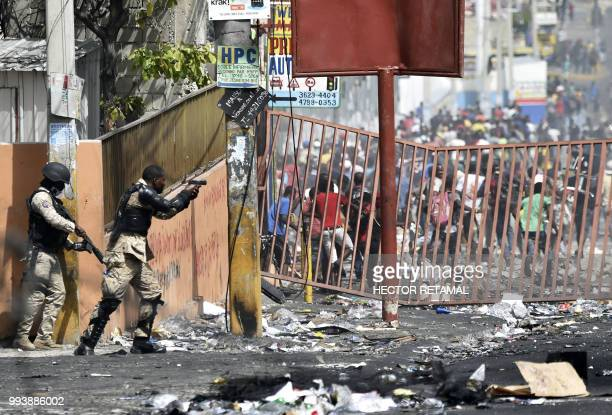 TOPSHOT A member of the Haitian police points his gun at people to avoid looting in shops in Delmas a commune near Port au Prince during protests...