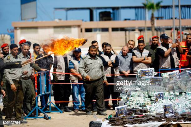 A member of the Hamas security forces sets fire to a pile of confiscated bars of hashish and analgesic pills seized since the beginning of the year...