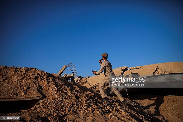 TOPSHOT A member of the Hashd Al Shaabi tries to spot the position of an Islamic State snipper at Tal Afar airport on November 20 2016 Progovernment...