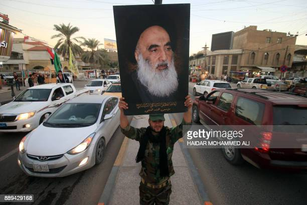 Member of the Hashed al-Shaabi carries a portrait of Iraqi Shiite cleric Grand Ayatollah Ali al-Sistani in a street in the southern city of Basra on...