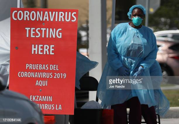 Member of the health care staff from the Community Health of South Florida, Inc. Prepares to test people for the coronavirus in the parking lot of...