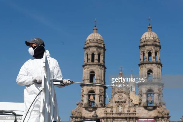 Member of the health personnel sanitizes outside the Basilica of Our Lady of Zapopan as part of the preventive measures against the spread of the...