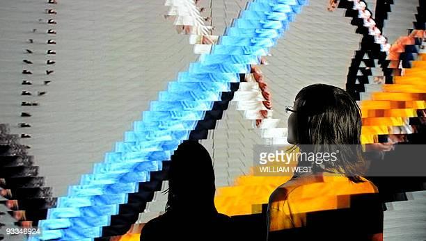 A member of the Heide Museum of Modern Art inspects a DVD projection by artist Daniel Crooks at an exhibition titled Cubism Australian Art a major...