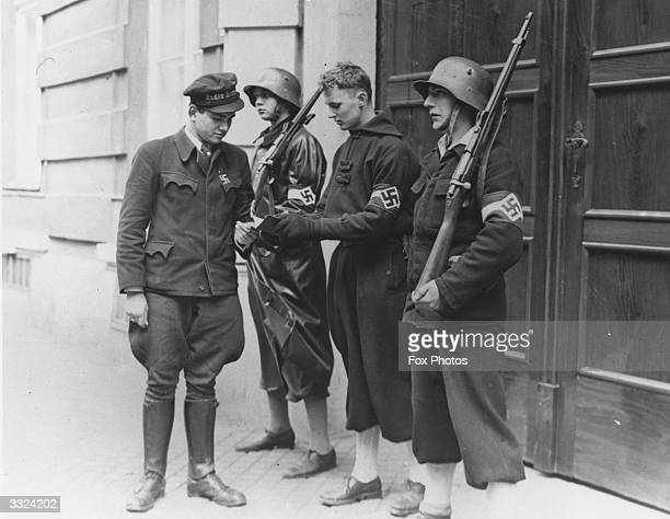 A member of the Hitler Youth in makeshift uniform intercepts a telegraph messenger at Vienna during the German occupation of Austria Members of the...