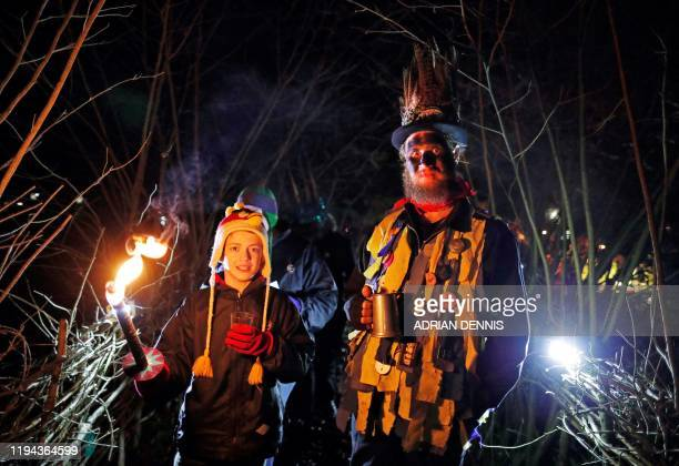 A member of the Hook Eagle Morris Men walks to the orchard with a villager to play music and sing during the annual Wassail night in Hartley Wintney...