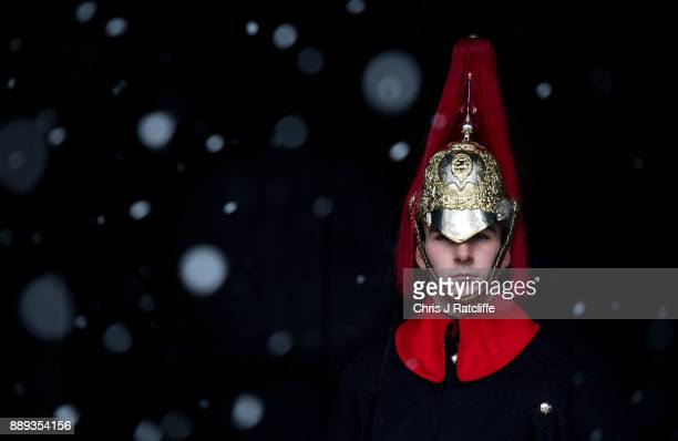 A member of the Household Cavalry is seen on guard at Horse Guard's Parade as snow falls briefly on the British capital on December 10 2017 in London...