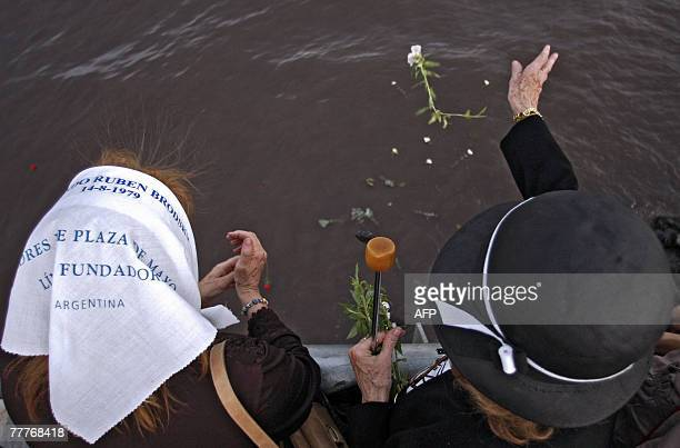 A member of the Human Rights organization Madres de Plaza de Mayo and another woman throw flowers into the River Plate next to the Monument to the...