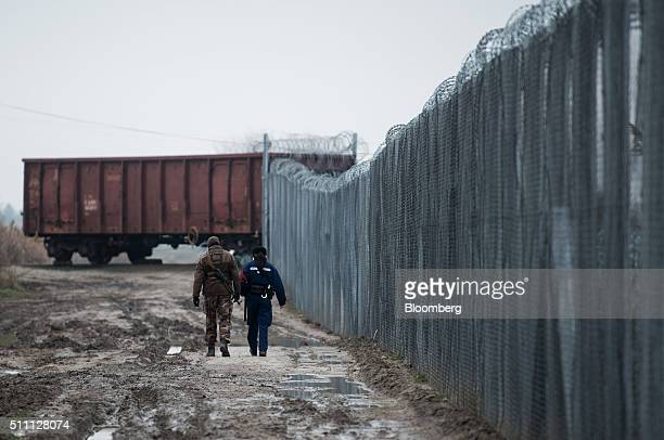 A member of the Hungarian military left and a member of the Hungarian police force patrol by the razor wired topped security fence on the...