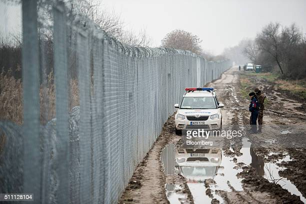 A member of the Hungarian military right and a member of the Hungarian police force speak to officers in a police force automobile as it patrols by...