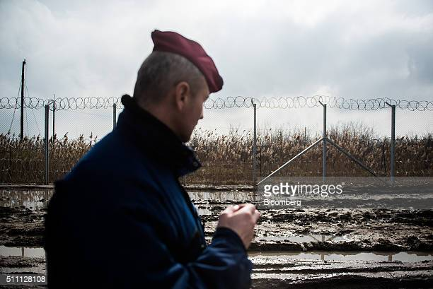 A member of the Hungarian police force patrols by the razor wired topped security fence on the HungarianSerbian border near Roszke Hungary on...
