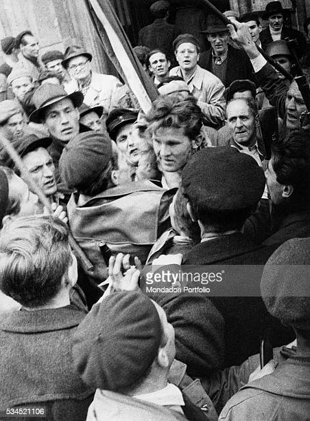 A member of the Hungarian secret police is surrounded by the enraged crowd after his capture during the revolt of the Hungarian people against the...