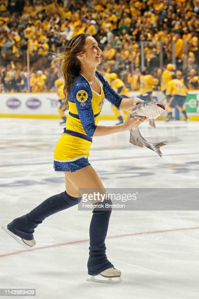Member of the ice crew carries away a catfish that was thrown onto the ice prior to the first period of Game Five of the Western Conference First...