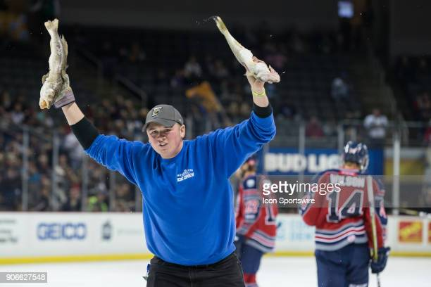 A member of the ice crew carries Walleye fish that were thrown onto the ice during a regular season ECHL hockey game between the Kalamazoo Wings and...