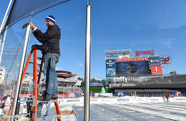 A member of the ice crew installs a remote microphone on the plexiglass during the 2015 Bridgestone NHL Winter Classic Build Out on December 30 2014...