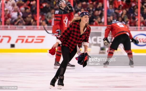 A member of the ice crew picks up hat after Morgan Frost of Canada scored his third goal of the game for a hat trick against Denmark in Group A...