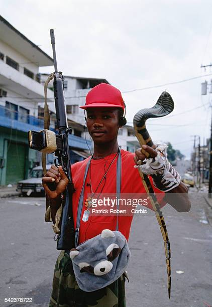 A member of the Independent National Patriotic Front of Liberia carries with him a children's bag and a wooden snake rebel forces often carry unusual...