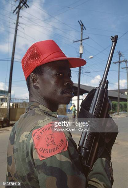 A member of the Independent National Patriotic Front of Liberia wears a patch reading 'Death before dishonor' Responding to years of government...
