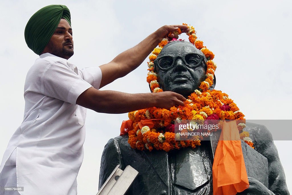 A member of the Indian Congress Party places flowers on a statue of Dalit icon Bhim Rao Ambedkar to mark the 122nd anniversary of his birth in...