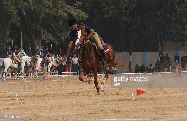 A member of the Indian Mounted Police participates in a tentpegging event on the eve of the All India Police Equestrian Meet at Ghoda Camp in...
