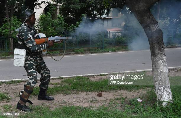 A member of the Indian security forces fires a tear gas canister during clashes between the controversial guru's followers and security forces in...