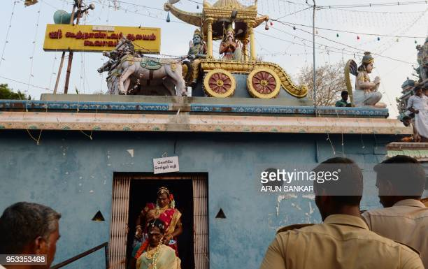 A member of the Indian transgender community dressed as a bride leaves a temple after taking part in a 'thali' ritual signifying marriage to the...