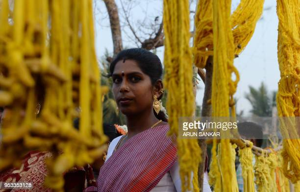 A member of the Indian transgender community dressed as a bride prepares to take part in a ritual signifying marriage to the Hindu warrior god Aravan...