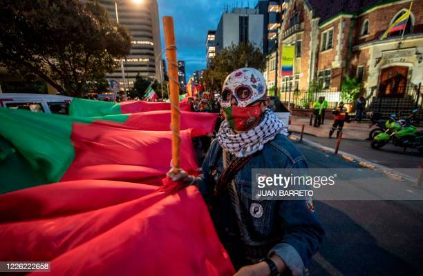 A member of the indigenous guard joined by union workers protests against Colombian President Ivan Duque and the alleged rape of indigenous girls by...